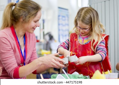 Nursery teacher helping a student cut an egg box in their crafts lesson.