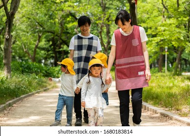 Nursery teacher and kindergarten walking in the park