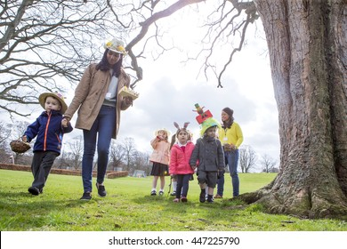 Nursery teachers and students doing an Easter egg hunt outdoors. They are wearing handmade hats and carrying baskets.