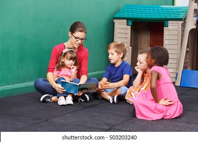 Nursery woman reading book for group of children in a kindergarten