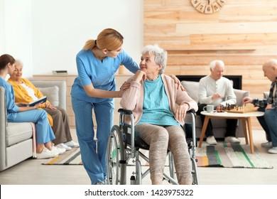 Nurses assisting elderly people at retirement home - Shutterstock ID 1423975322