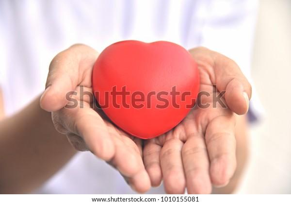 Krankenschwestern, die Rotes Herz in zwei Händen halten und pflegen. Good Health Support and Protection Business Hospital Private Service Concept.Cross Processing und Split Ton Instagram like Process.