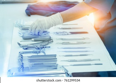 Nurses are holding medical instruments after cleaning.Medical instruments for cosmetic surgery on white cloth backgrond.Cleaning of medical instruments after use.Dental Clinic
