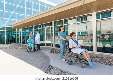Nurses and male doctor with patients on wheelchairs at hospital courtyard