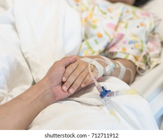 Nursing caretaker concept with kid patient sleeping in bed with family caregiver hand support in blur medical hospital background (focus on hand)