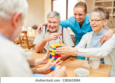 Nursing home care in demente seniors while playing with building blocks