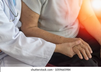 Nursing home with Geriatric doctor or geriatrician concept.Doctor physician hand on happy elderly senior patient to comfort in hospital examination room or hospice nursing home or hospice county.