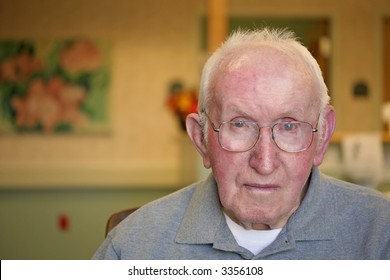 """Nursing Home Portrait (serious look)"" Elderly man with a serious look, dimly lit environment."