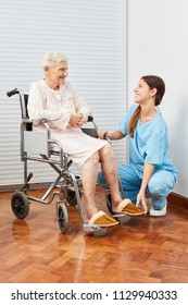 Nursing lady helps elderly woman to put on slippers in nursing home
