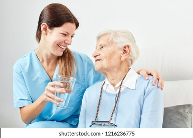 Nursing service Woman gives senior citizen in the nursing home a glass of water or a medicine