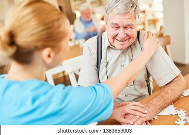 Nursing woman consoles a senior with dementia in geriatric care at nursing home