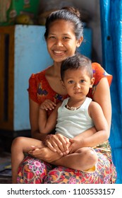 NUSA PENIDA, INDONESIA, JANUARY 12, 2018 : A young mom is posing with her son at home in a small village of Nusa Penida island near Bali, Indonesia