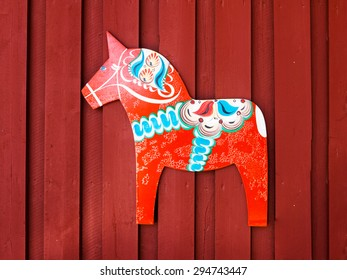 NUSNAS, DALARNA, SWEDEN - JUNE 20, 2015: Dalarhest, traditional wooden horse, tablet on the copper red wooden wall of traditional rural house