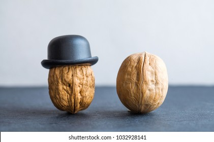 Nut gentleman walnut black hats on stone background. Creative food design poster. Macro view selective focus photo.