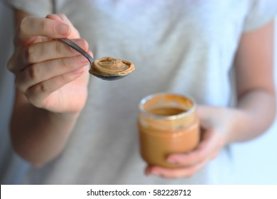 Nut paste in female hands on a light background.
