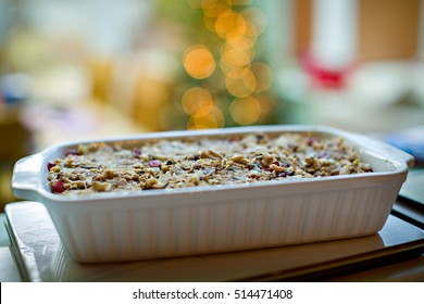 Nut roast in a baking dish with narrow depth of field and bokeh from Christmas tree lights in the background. Healthy vegetarian Christmas dinner.