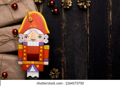 Nutcracker toy with gifts with a New Year's decor on a wooden background