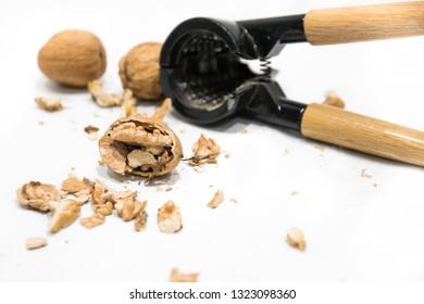 Nutcracker, walnut kernel peeled and whole nutshells, isolated on a white background. Dried fruit