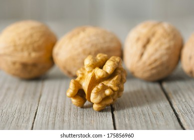 nutmeats and walnuts on weathered wooden table background