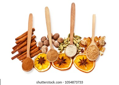 Nutmeg, cinnamon, cardamom, brown sugar, anise star, slices of dried orange and powder of nutmeg, cinnamon, cardamon, brown sugar in a wooden spoons isolated on white background. Top view.