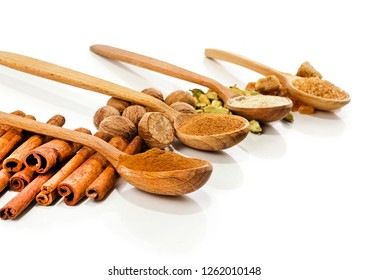 Nutmeg, cinnamon, cardamom, brown sugar and powder of nutmeg, cinnamon, cardamon, brown sugar in a wooden spoons isolated on white background.