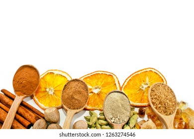 Nutmeg, cinnamon, cardamom, brown sugar, slices of dried orange and powder of nutmeg, cinnamon, cardamon, brown sugar in a wooden spoons isolated on white background. Top view.