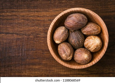 Nutmeg, close-up, aromatic spice, wooden background