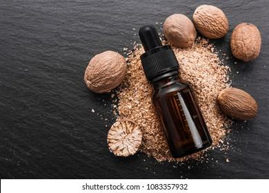 nutmeg essential oil on a dark stone background.