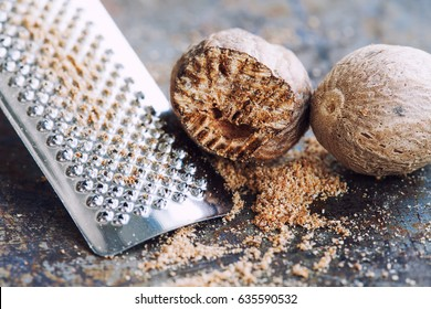 Nutmeg grater macro view. Kitchen still life photo close-up muscat nut powder. Shallow depth of field, vintage brown rusty background. Selective focus.