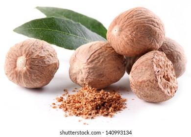 Nutmeg with leaves on a white background.