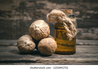 Nutmeg oil in the bottle and pile of nuts on the wooden table background.