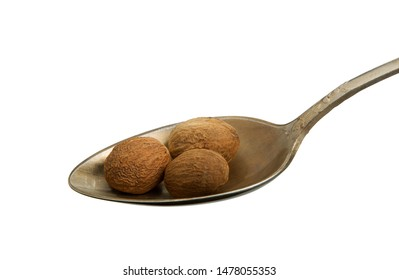Nutmeg in an old spoon isolated on a white background. Seasoning on isolate. View from above. Close up view of nutmeg.
