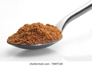 nutmeg in a spoon on white background