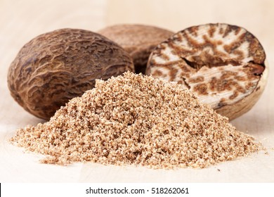 Nutmeg , whole , half and ground  on wooden plank, close up
