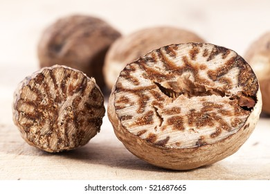 Nutmeg , whole and half on wooden plank, close up