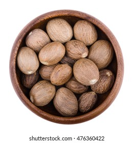 Nutmegs in a wooden bowl on white background. Myristica fragrans, also called pala, an edible brown and egg-shaped seed of a tree, culinary use as spice. Isolated macro photo close up from above.