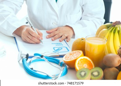nutrionist writing a diet plan on table