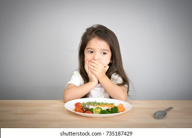 Nutrition & healthy eating habits for kids concept. Children do not like to eat vegetables. Little cute kid half race girl refuse to eat healthy vegetables.