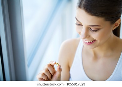 Nutrition. Healthy Lifestyle. Woman Holding Pill With Fish Oil Omega-3. Supplements, Vitamins.