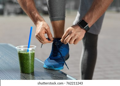 Nutrition. Male Legs With Healthy Detox Drink At Outdoor Workout. Close Up Of Green Vegetable Smoothie In Plastic Cup, Shoe And Smart Watch On Hand. Healthy Lifestyle. High Resolution.