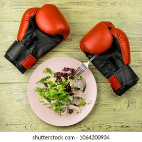 Nutrition for sports, healthy active way of life. Vegetarian salad of fresh vegetables and boxing gloves on a wooden background.