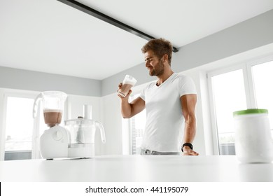 Nutrition Supplements. Handsome Happy Smiling Man With Muscular Body Drinking Protein Shake Before Workout. Sexy Athletic Fitness Male Model Enjoying Sports Drink Indoors. Bodybuilding, Healthy Eating