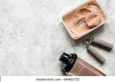 nutrition for workout with protein cocktail powder and bars on stone background top view mockup