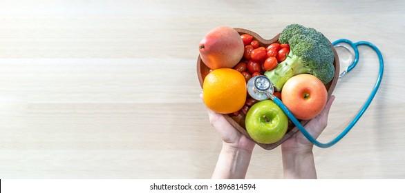 Ernährung für Wellness im Herzen durch Cholesterinernährung und gesunde Ernährung mit sauberem Obst und Gemüse in der Herzschale von Ernährungswissenschaftler und Arzt empfohlen für das Wohlbefinden der Patienten