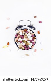 Nutritional supplement color pills on black alarm clock face isolated on white background with copy space. Template for feminine beauty blog social media. Female healthcare concept