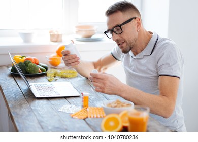 Nutritional supplements. Pleasant active positive man scrutinizing biohacking supplements while wearing glassed and holding bottles