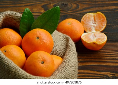 Nutritional Value of a Clementine. A lot of Clementines,orange or citrus in sack bag on wooden background.