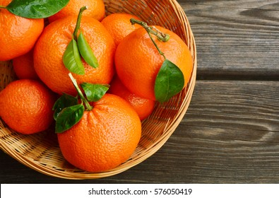 Nutritional Value of a Clementine. A lot of Clementines,orange or citrus with leaves  in basket on wooden background.