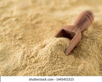 Nutritional yeast background. Nutritional inactive yeast with small wooden scoop. Copy space. Nutritional yeast is vegetarian superfood with cheese flavor, for healthy diet