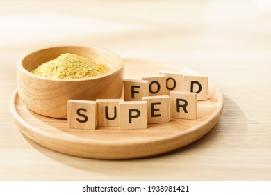 """Nutritional yeast flakes in a bowl with wooden letters """"Super Food"""". Vegan, Vegetarians and plant-base diet rich nutrients substitute protein source. Close up, Supplements, Superfoods concept."""